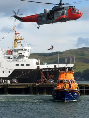 Man being winched from a lifeboat to a helicopter with a ferry in the background