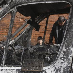 A man and boy look through the windows of a burnt-out car