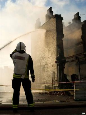 Firefighters dampen down a building in Tottenham, north London.