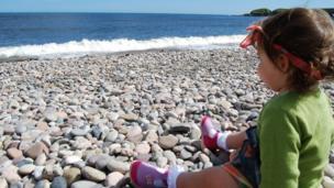 Juliet sitting on pebbles on the beach