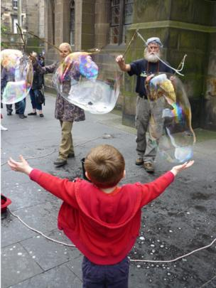 Boy watching people blowing bubbles on the pavement