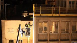 Two graffiti artists on a crane spray paint the top of a high rise building in Bristol.