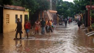 People walking through flood water on the streets of San Cristobal in Hispaniola.