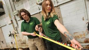 Zookeepers hold a tape measure up against a milk snake to check it's size.
