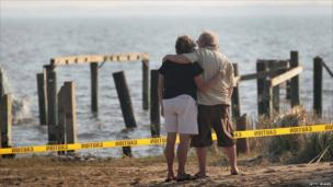 Billy Stinson (right) is comforted by Gayle Felton as he looks at the remains of his cottage in Nags Head, North Carolina, on 28 August 2011