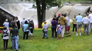 Residents in Windsor, New Hampshire, watch as water rushes over the Ascutney Mill Dam on Kennedy's Pond, on 28 August 2011