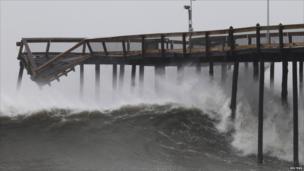 Waves break along the damaged pier in Ocean City, Maryland, on 28 August 2011