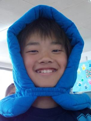 A school child wearing a blue cushioned hood.