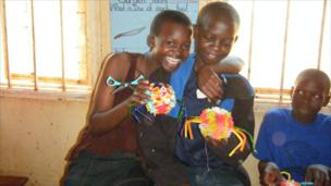 Ugandan children holding some woollen spiders they have made in a craft class