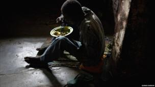 A prisoner at Liberia's Monrovia Central Prison eats a bowl of rice - 2011