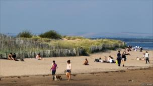 Walkers on St Andrews beach in Scotland