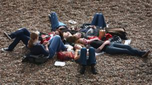 Friends relaxing in the warm weather on a beach in Brighton, East Sussex