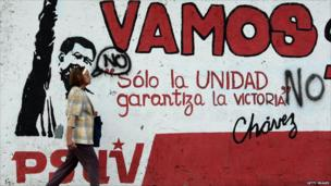 A woman walks in front of a mural painting during the referendum on a constitutional amendment, in Caracas on 15 February 2009.