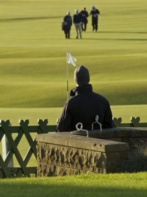 Man watching golfers on the Old Course at St Andrews