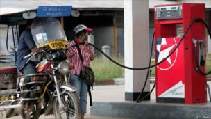 A petrol station worker fills a 'tuk-tuk'