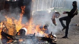 Protesters feed a fire from the remains of a burnt caravan during evictions from Dale Farm travellers camp on 19 October, 2011