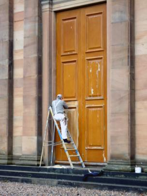 Man on a ladder painting a door