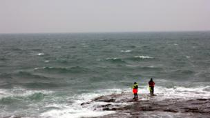 Fishermen standing on rocks