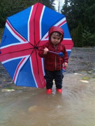 Child with umbrella in a puddle
