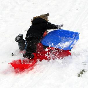 Children fall off sledges in the snow