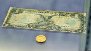 US dollar banknote, soiled with dirt and stains.