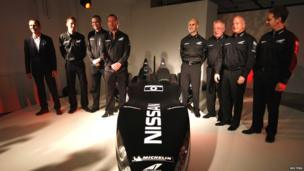 Nissan's new Deltawing race car is seen after it was unveiled in London. A team of designers in smart black overalls stand proudly beside their creation.
