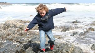 Alistair running from an incoming wave