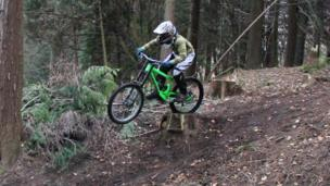 A young person on a mountain bike in some woods