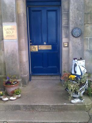 Flowers in golf equipment on a doorstep