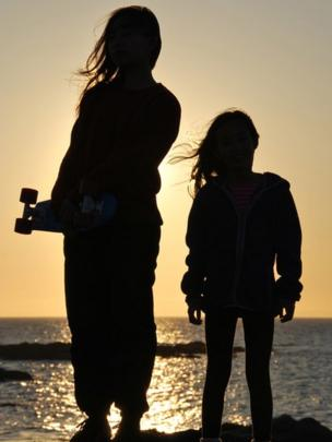 Silhouette of two girls by the shore