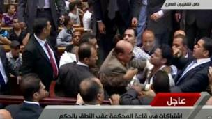 Egyptian state TV shows people scuffling inside a courtroom at the end of the verdict.
