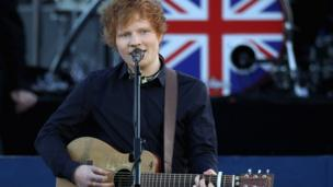 Ed Sheeran performing on stage in front of Buckingham Palace