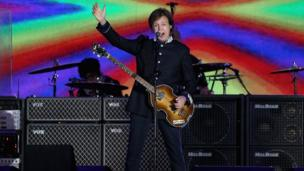 Sir Paul McCartney performing on stage in front of Buckingham Palace