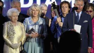 The Queen, Duchess of Cornwall, and Sir Paul McCartney standing next to the Prince of Wales as he gives a speech