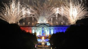 fireworks and beacon light up Buckingham Palace
