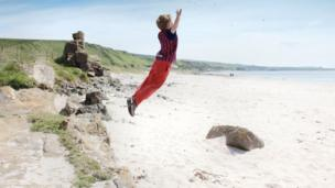 Tom jumping on the beach