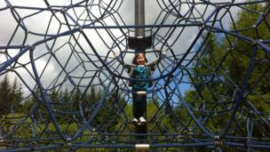 Evie on a rope climbing frame