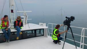 Joe on a boat talking to an expert about wind farms