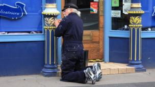 Jake Brown painting a shop front