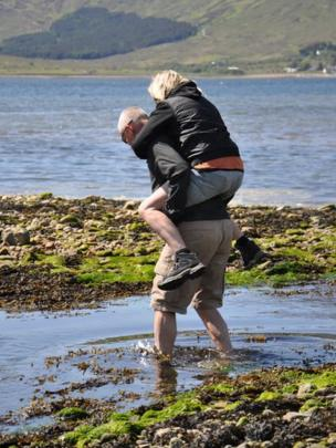 A woman gets a piggyback to cross water