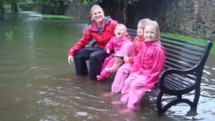 Isla, Maisie and Isobel and mum Jo sitting on a park bench