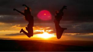 Girls jumping at sunset