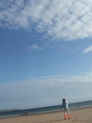 Girl flying a kite on a beach
