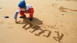 Boy writing in the sand