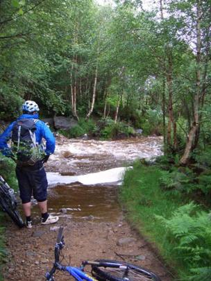 Simon standing by a fast flowing stream