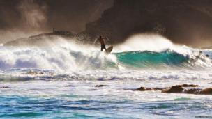 A surfer at Sandy Beach next to Koko Crater on the island of Oahu, Hawaii.