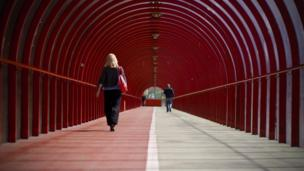 People walking through a covered walkway