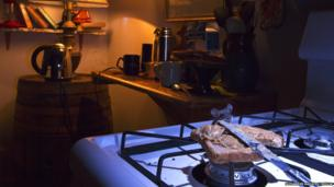 A mouse nibbles on some peanut buttered toast in a kitchen.