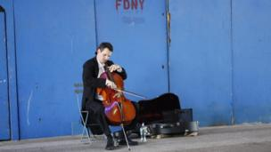 A man plying a cello in front of a blue wall