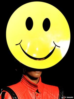 Model wearing a yellow smiley face hat.